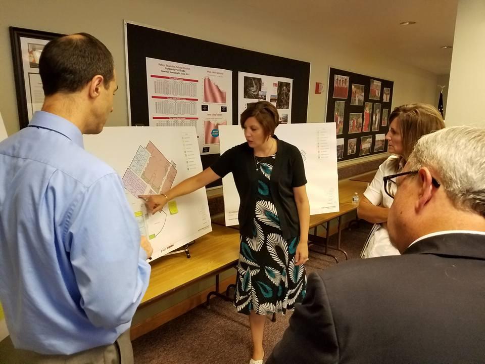 Mrs. Pavlik shares the design as board members look on.