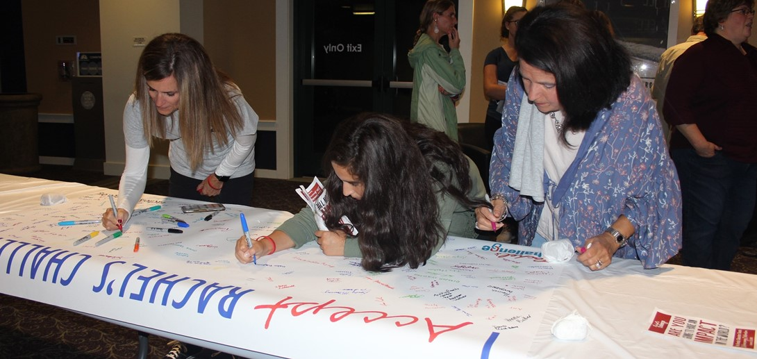 Community members sign the banner saying they accept the kindness challenge at the event.