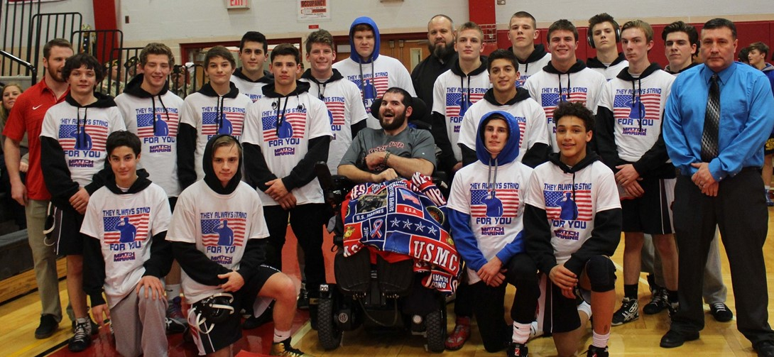 Student wrestlers stand with injured Marine Doug VItale.