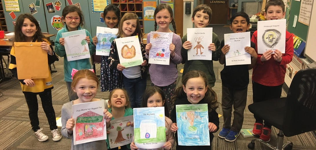 Students pose holding the books they wrote and illustrated.