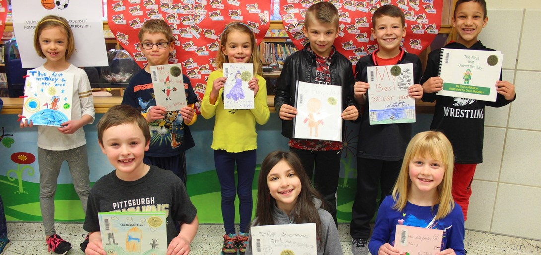 Student authors holding their books