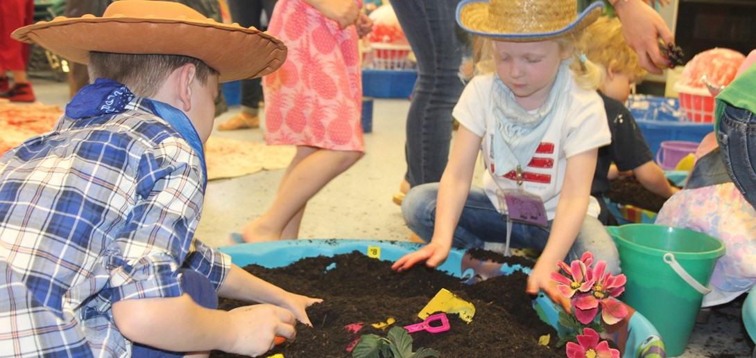 Students digging in the dirt on farm day.