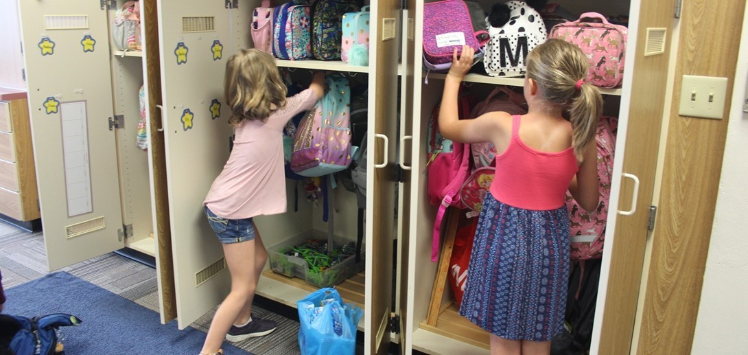 Students put supplies in their cubbies at school