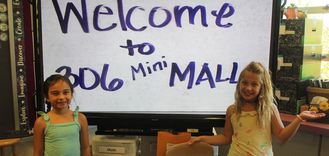 Students in front of a Mini-mall sign.