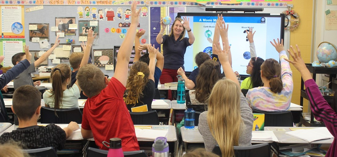 Students raise their hands to answer a question in class.