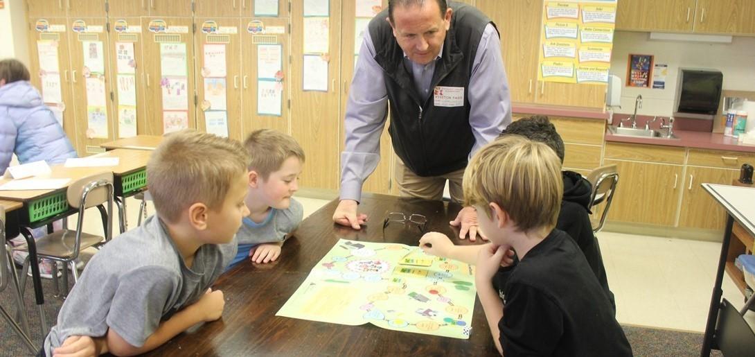 JA volunteers talks with students during lesson.