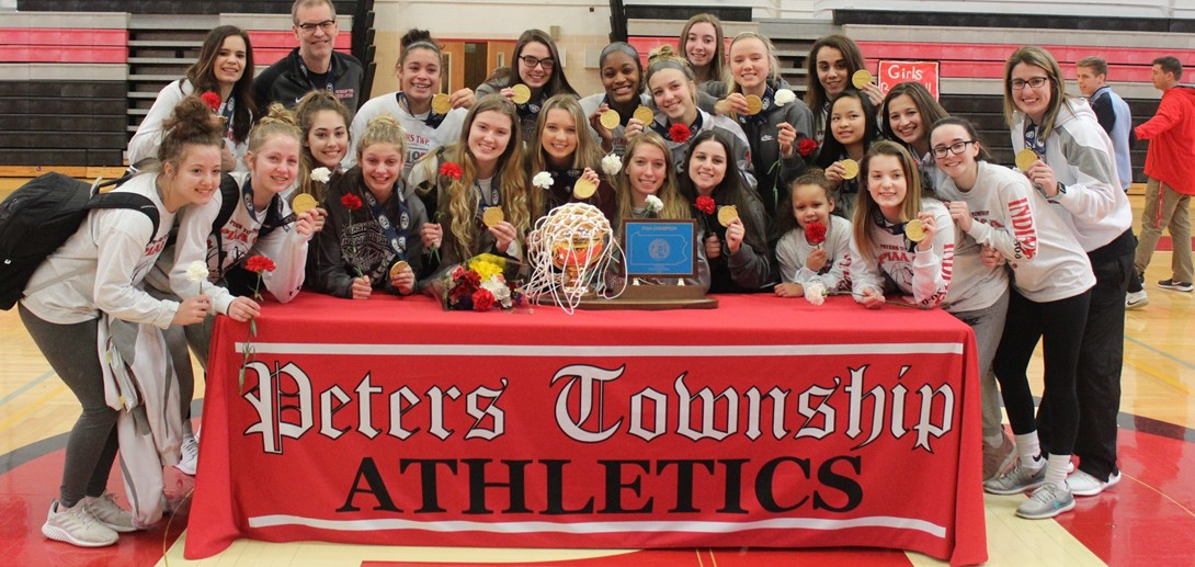 Girls basketball team with trophy and medals from state win.