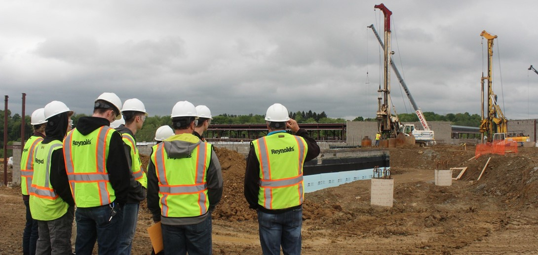 students in hard hats at the construction site.