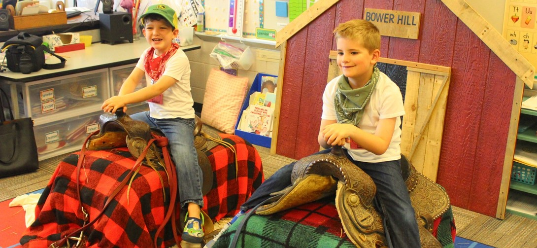 Students take photos on fake horses during farm day.