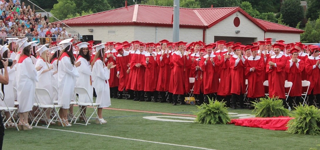 Students give the teacher speaker a standing ovation at graduation.