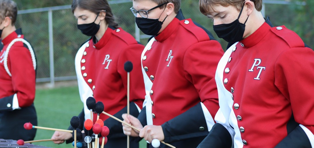 Marching band students in uniform.