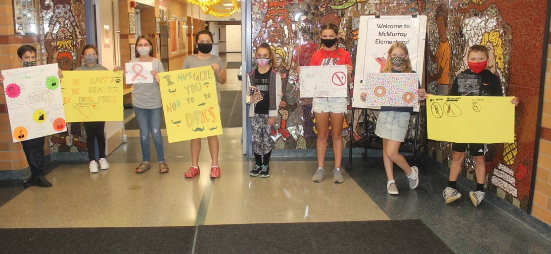 Red ribbon week winners holding posters.