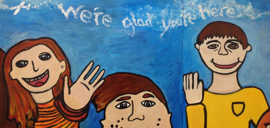 Student mural with images of students waving hello.