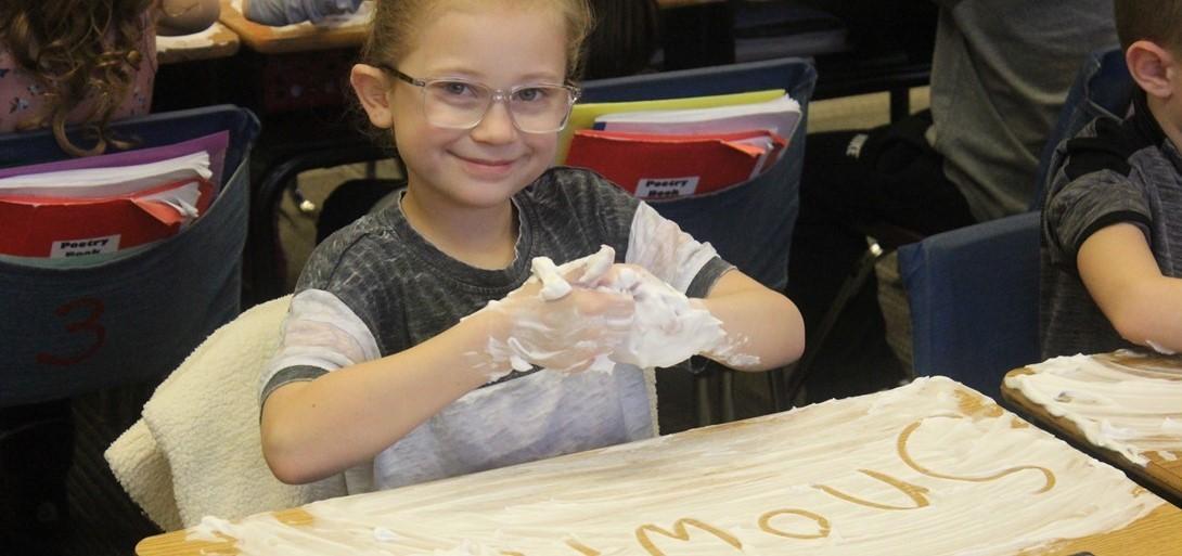 First grader writes winter words in shaving cream on her desk.