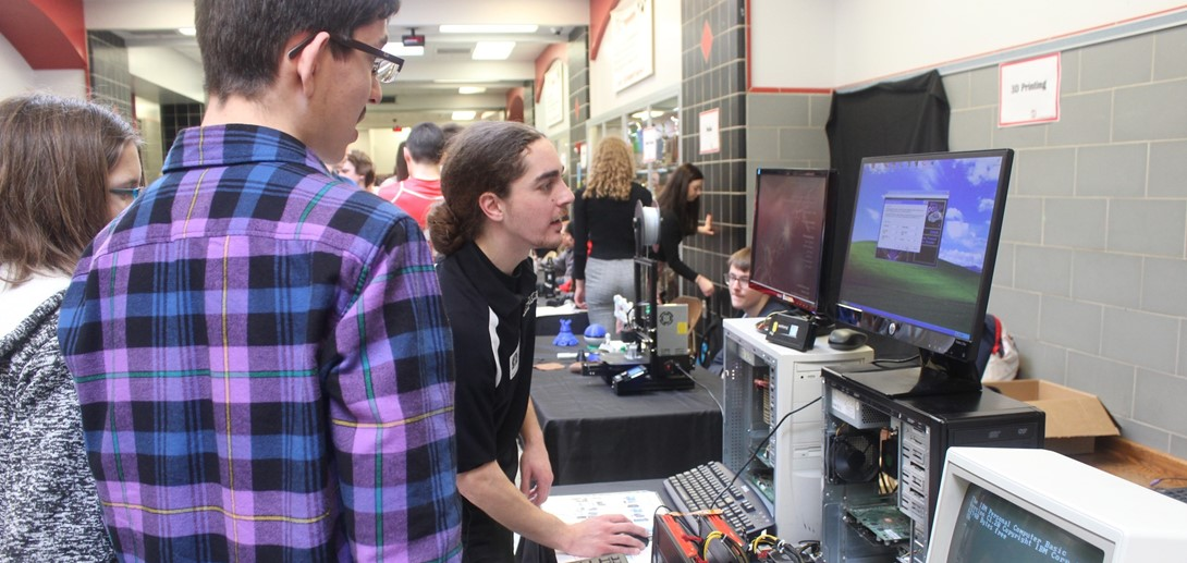 students talk with a vendor at technology day