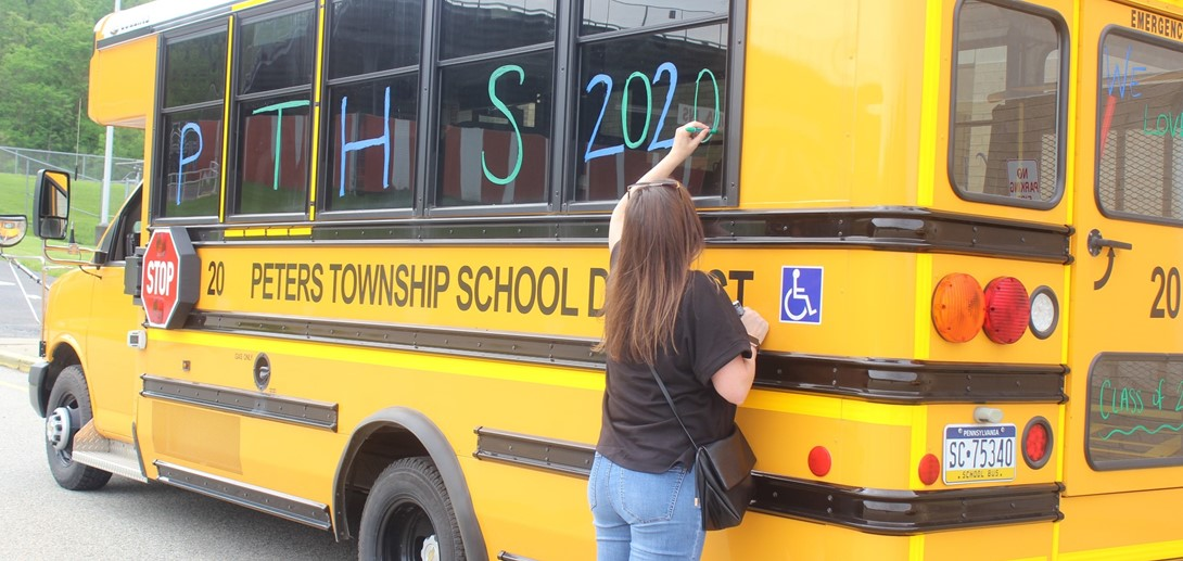 Staff member decorates school bus.
