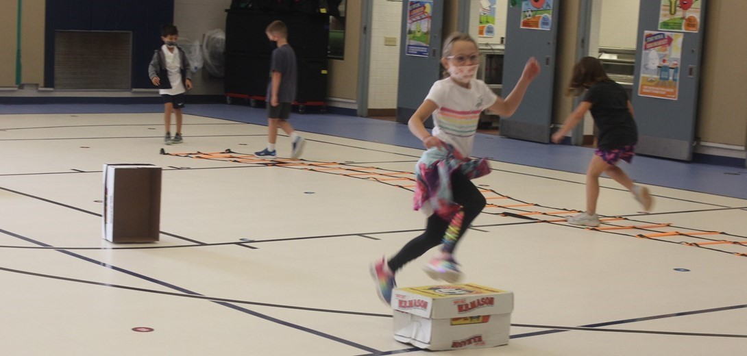 Students jumping over boxes in an obstacle course