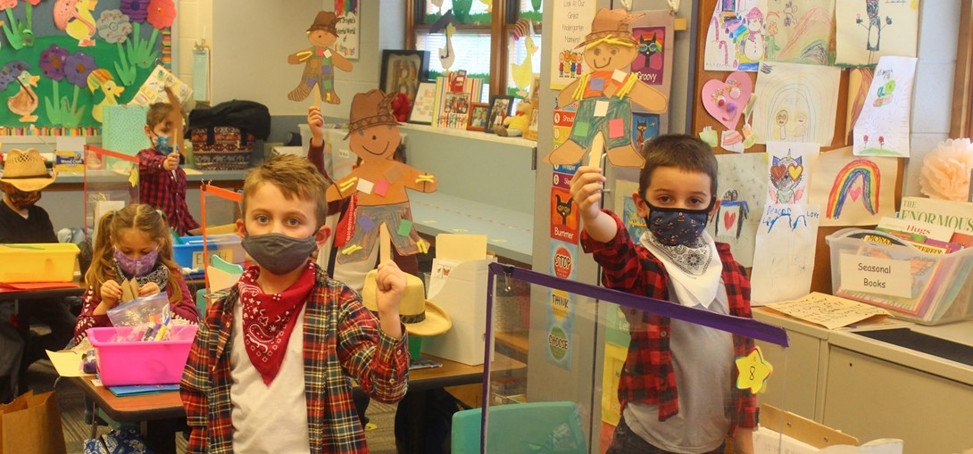 Students hold up their scarecrows